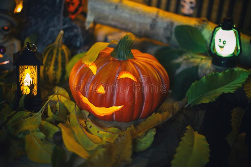 Halloween decorations concept at night. Close up of jack o`lantern, vintage lanterns, pumpkins, skull, autumn leaves stock image