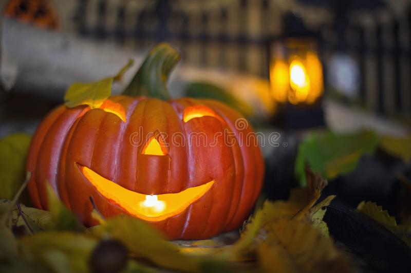 Halloween decorations concept at night. Close up of jack o`lantern, vintage lanterns, pumpkins, skull, autumn leaves royalty free stock photography