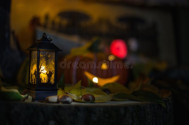 Halloween decorations concept at night. Close up of jack o`lantern, vintage lanterns, pumpkins, skull, autumn leaves royalty free stock image