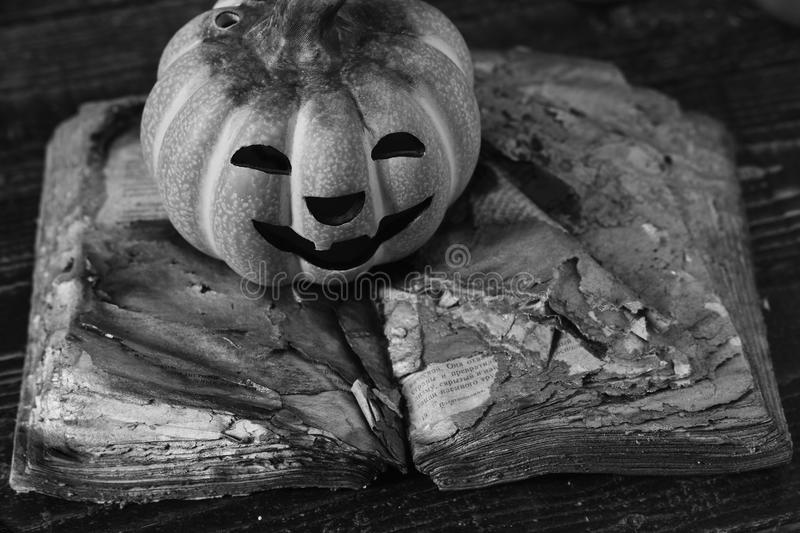 Halloween decorations concept. Pumpkin with happy carved face lies on old open book stock photography