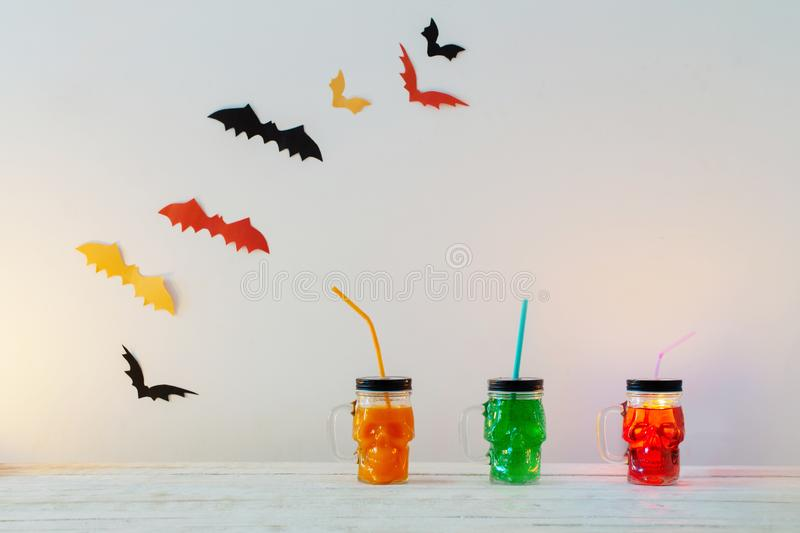 Halloween decorations with drinks in mug in form of skull stock photo