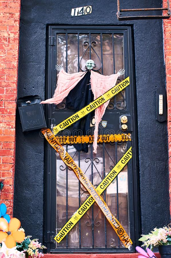 Halloween decorations including a witch and decorative police stripes on the front door of a house in Brooklyn, New York stock photos
