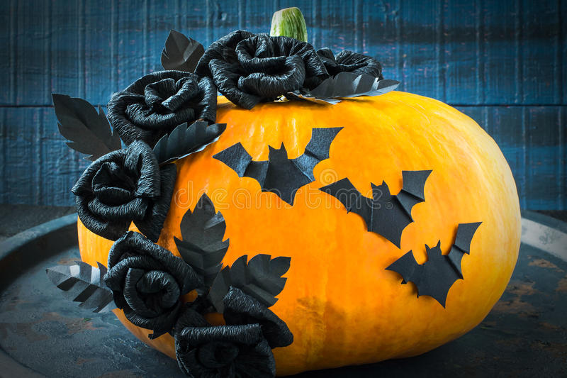 Halloween design. Black roses and bats made of paper on a pumpkin royalty free stock photos