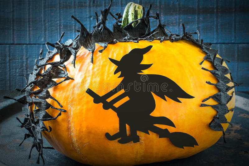 Halloween design. Tape and the witch of black paper on the pumpkin stock photos
