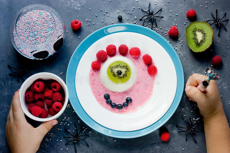 Halloween dessert recipe scary fun and tasty one-eyed monster jelly panna cotta with fruit. Creative idea for kids party royalty free stock photography