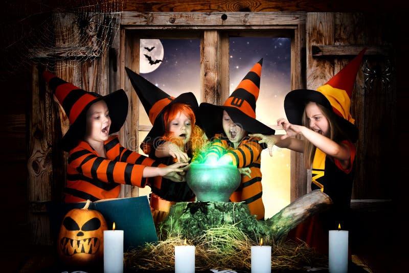 Halloween Die Kinder von den Hexen und von Zauberern, die Trank im Großen Kessel mit Kürbis und Bannbuch kochen lizenzfreie stockfotos