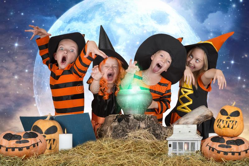 Halloween Die Kinder von den Hexen und von Zauberern, die Trank im Großen Kessel mit Kürbis und Bannbuch kochen lizenzfreie stockfotografie