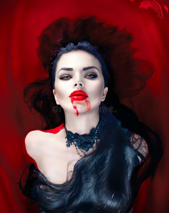 Halloween Donna del vampiro che si trova in un bagno in pieno di sangue fotografia stock libera da diritti