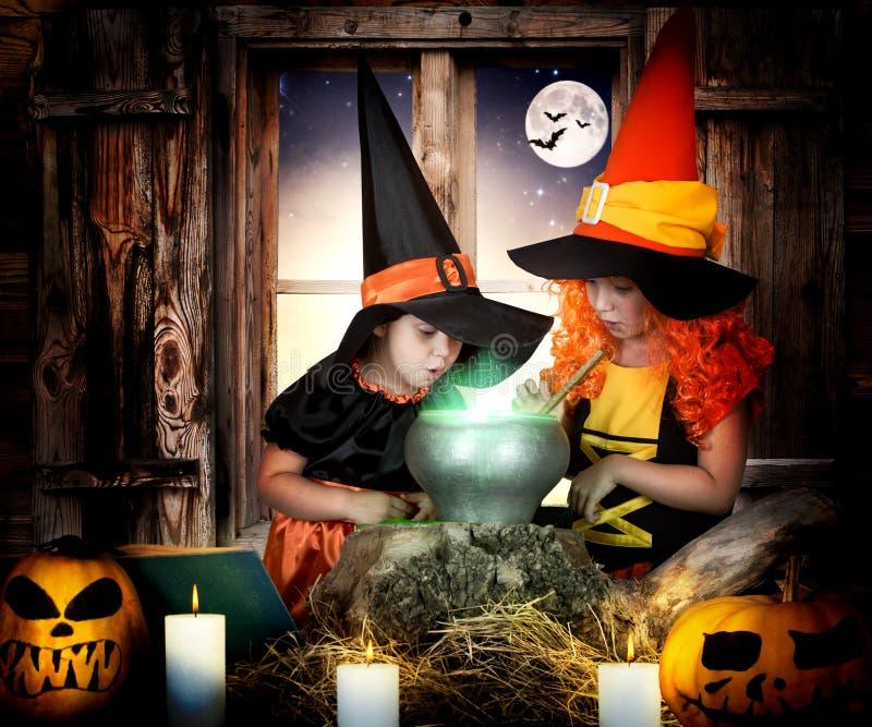 Halloween Duas bruxas pequenas das irmãs que cozinham a poção no caldeirão com abóbora e livro do período imagens de stock