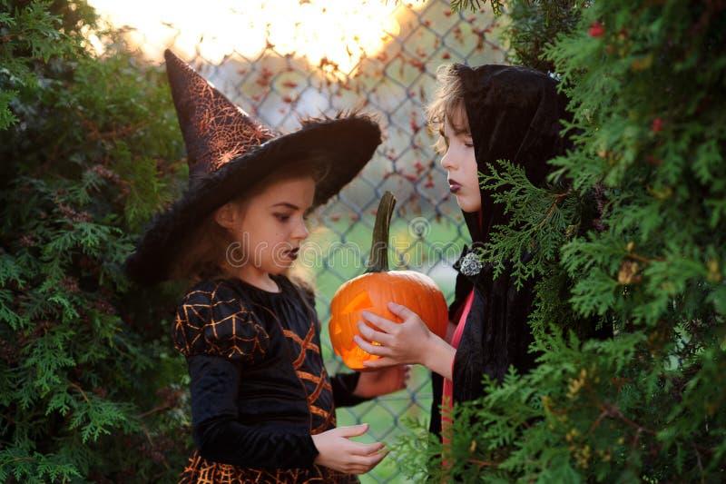 Halloween Duas crianças que representam o personagem sinistro escondem nos arbustos fotos de stock