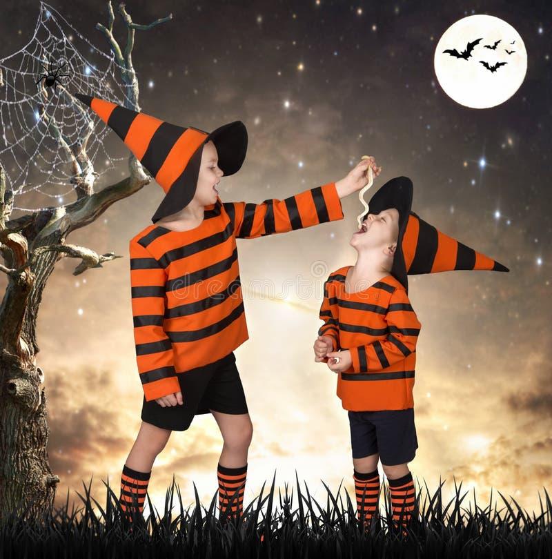 halloween Dwa brata w kostiumowym odprowadzeniu w straszni drewna Chłopiec karmi jego brata węża zdjęcie stock