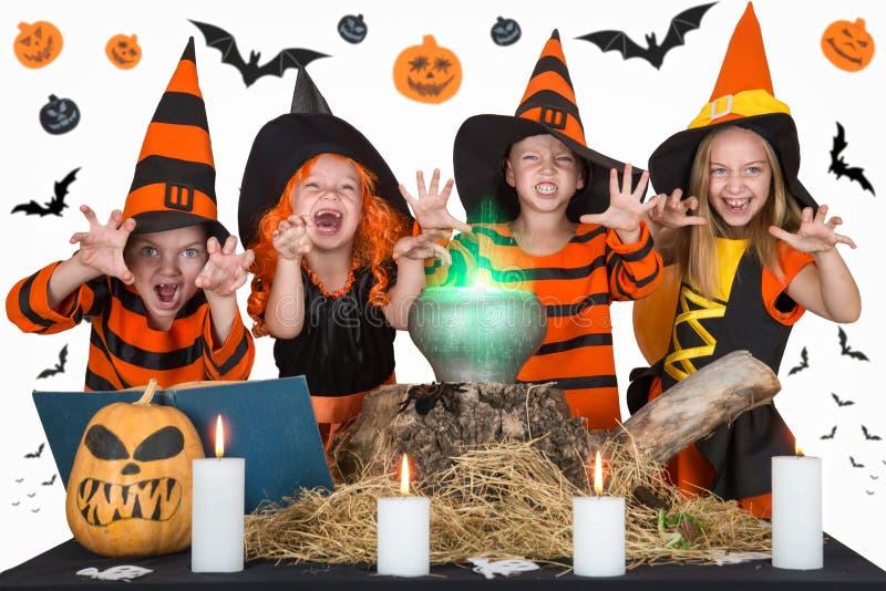 halloween Dzieci czarownicy i czarownicy gotuje napój miłosnego w kotle z banią i czary książką fotografia stock