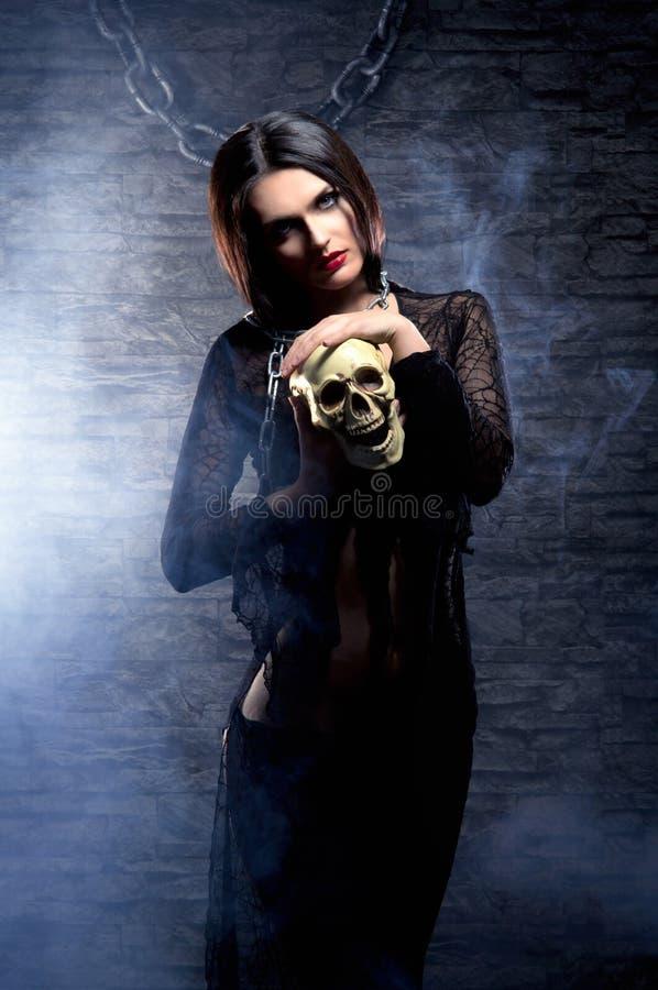 Halloween: een jonge en sexy heks met een schedel stock fotografie