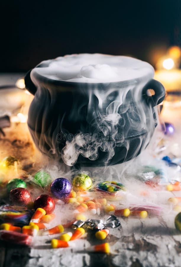 Halloween: El caramelo rodea la caldera con la poción mágica foto de archivo