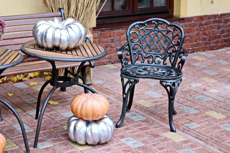 Halloween-element - pompoenen en bloemen met heksen` s bezem op de lijst en de vloer stock afbeeldingen