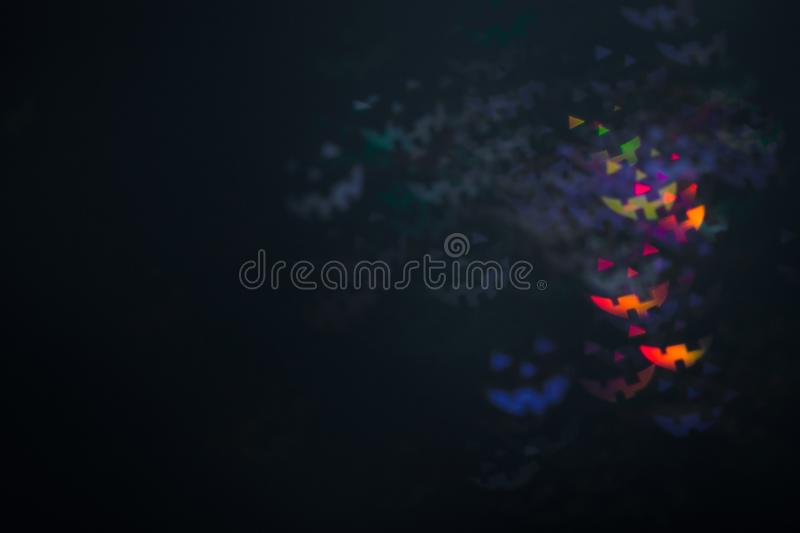 Halloween emoticons as abstract glowing blurred background. Defocused blinking shaped lights bokeh. Background for halloween product royalty free stock photography