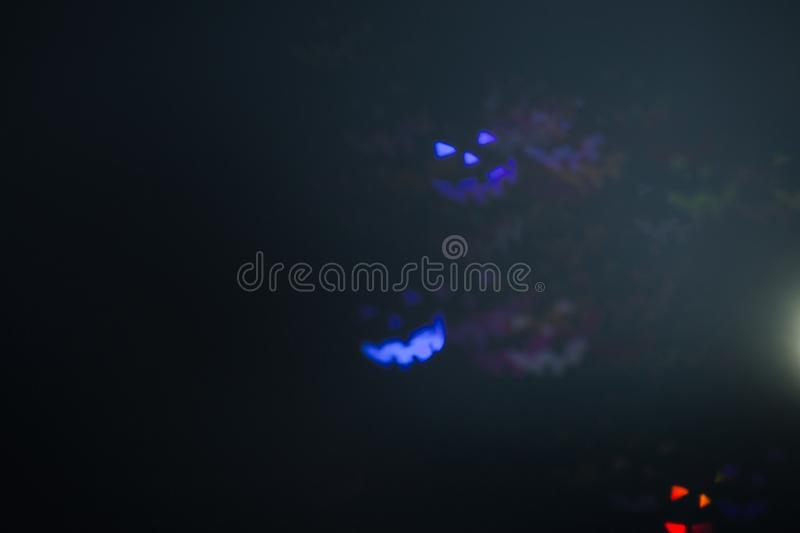 Halloween emoticons as abstract glowing blurred background. Defocused blinking shaped lights bokeh. Background for halloween product stock images