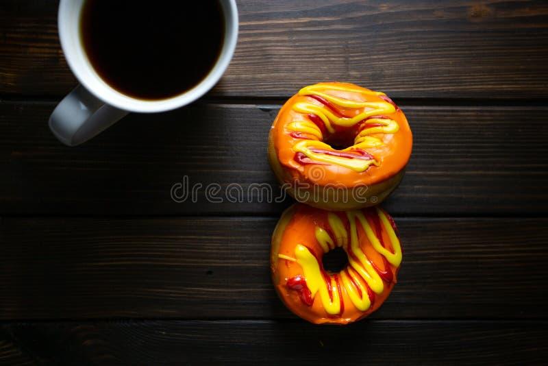 Halloween et automne ont coloré les butées toriques colorées savoureuses servies au petit déjeuner sur une table de cuisine avec  photo libre de droits
