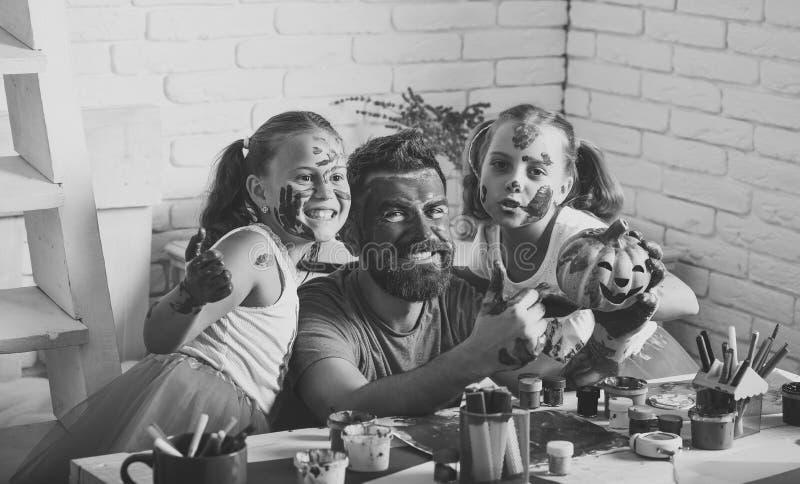 Halloween-familie van de mens en meisjes in verf met pompoen stock afbeeldingen