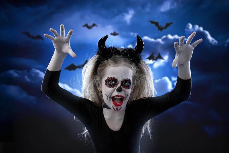 Halloween, Feiertage, Maskeradekonzept - das Porträt des jungen kleinen schönen Mädchens mit Schädelmake-up auf Himmelnachthinter stockbild