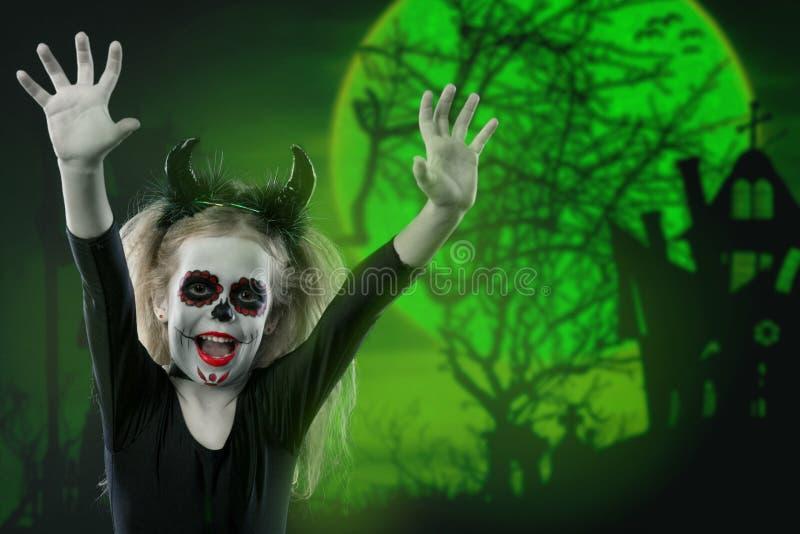 Halloween, Feiertage, Maskeradekonzept - das Porträt des jungen kleinen schönen Mädchens mit Schädelmake-up und Hörner Halloween, lizenzfreie stockfotos