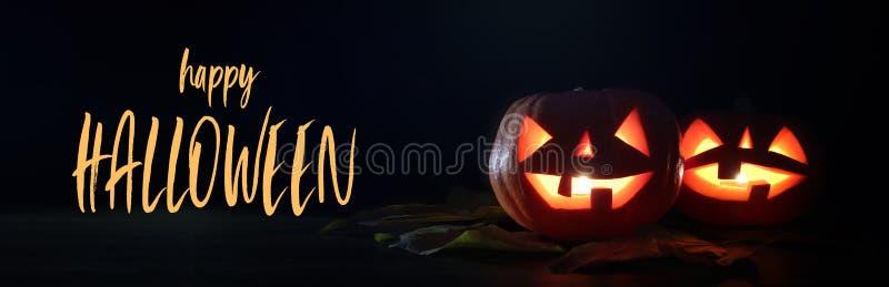 Halloween-Feiertagskonzeptfahne Kürbise über Holztisch am Nachtfurchtsamen, frequentierten und nebelhaften Wald stockfoto