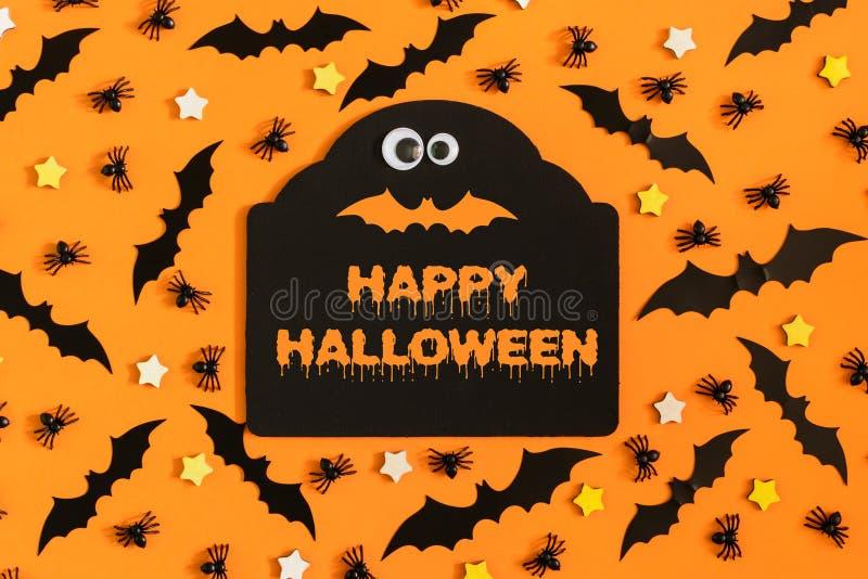 Halloween felice Molti stelle dell'ornamentale, piccoli ragni e pipistrelli sono allineati con fondo arancio Nel centro c'è immagini stock libere da diritti