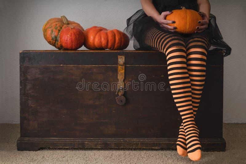 Halloween felice! Piedi femminili in calze con una zucca arancio immagine stock