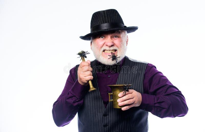 Halloween feliz feiticeiro mau que cozinha a poção mágica com aranha traje do feriado do Dia das Bruxas o empregado de bar faz o  imagens de stock royalty free