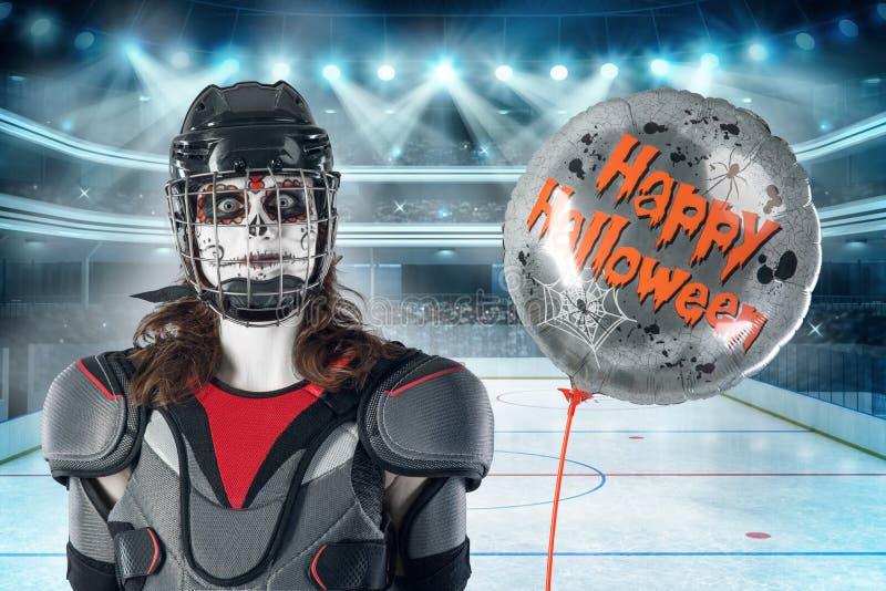 Halloween feliz jogador de hóquei em um capacete e em uma máscara do hóquei com um balão contra o contexto ou fundo de um campo d imagem de stock