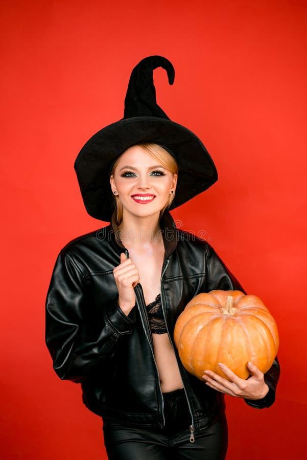 Halloween feliz Jovens mulheres em trajes pretos do Dia das Bruxas da bruxa no partido sobre o fundo vermelho imagens de stock