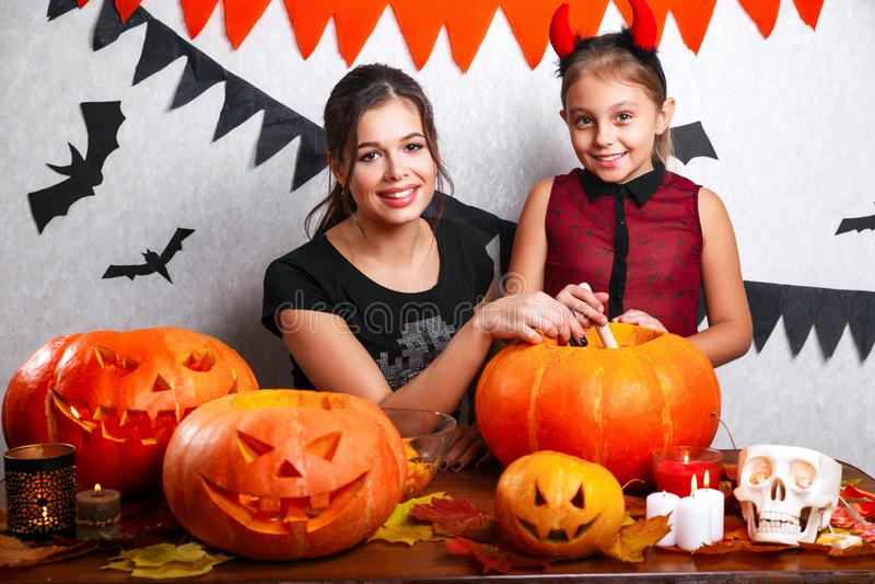 Halloween feliz Mãe e filha que cinzelam a abóbora Família que prepara-se para o feriado fotografia de stock