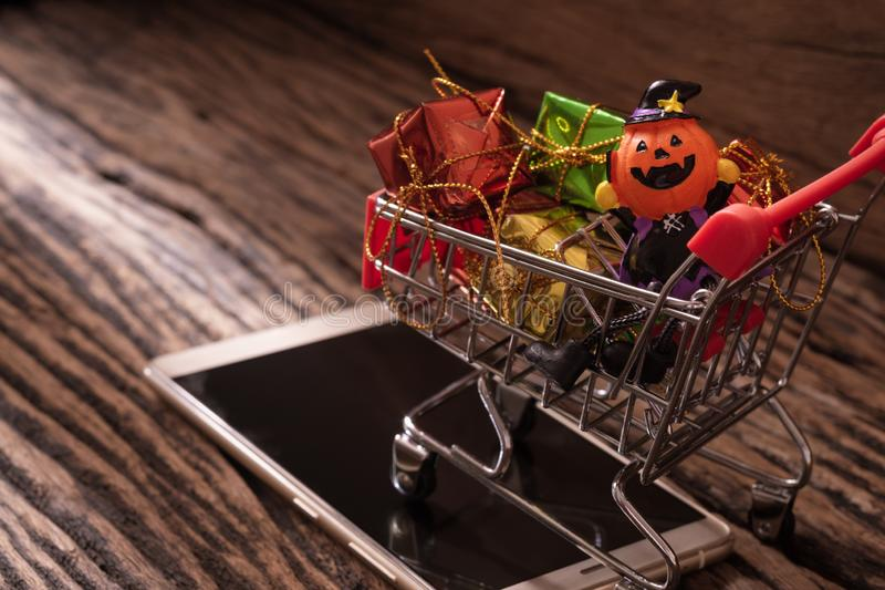 Halloween festival online mobile shopping concept. Halloween pumpkins with shopping cart and smartphone on wood background. royalty free stock photo