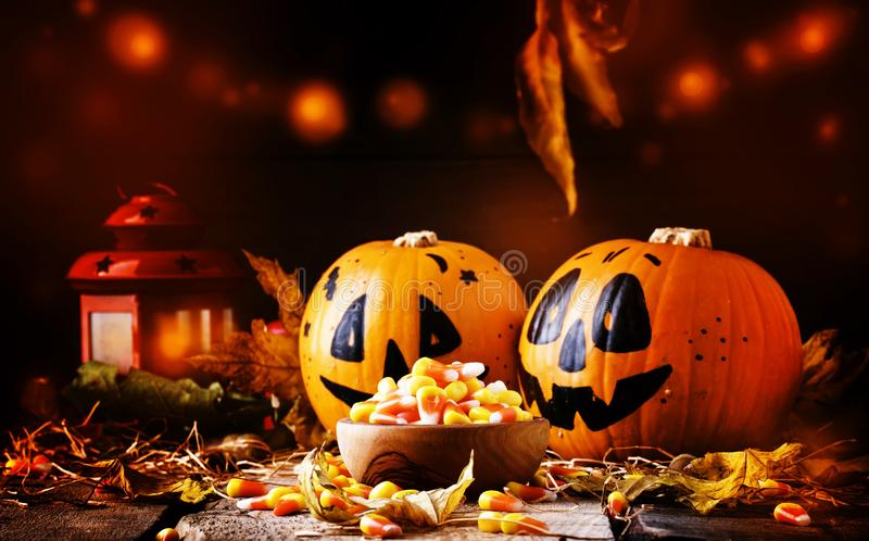 Halloween festive composition with sweet corn in bowl and smiling pumpkins guards, lantern, straw and fallen leaves on dark royalty free stock images