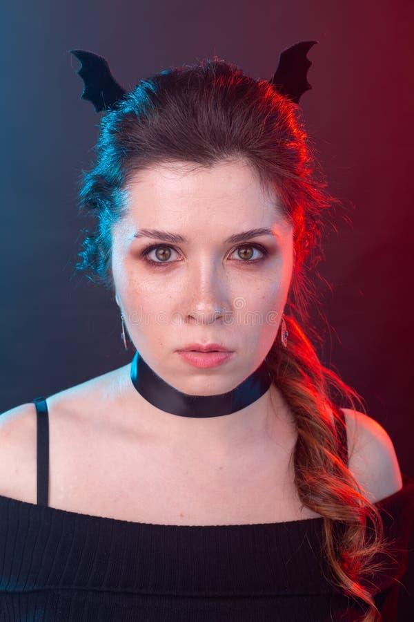 Halloween, fiestas y concepto de carnaval - Vamp mujer en las orejas de cuello y murciélago en estilo gótico fotografía de archivo