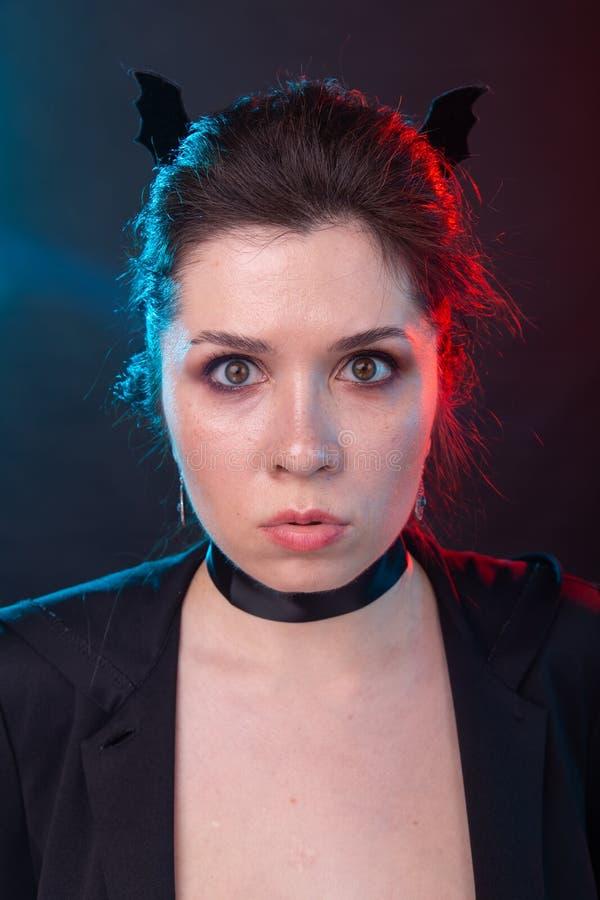 Halloween, fiestas y concepto de carnaval - Vamp mujer en las orejas de cuello y murciélago en estilo gótico imagen de archivo libre de regalías