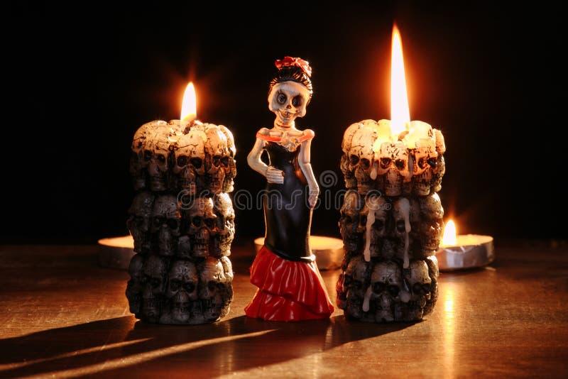 Halloween: figure di singoli scheletri della donna contro lo sfondo delle candele brucianti sotto forma di fotografia stock libera da diritti