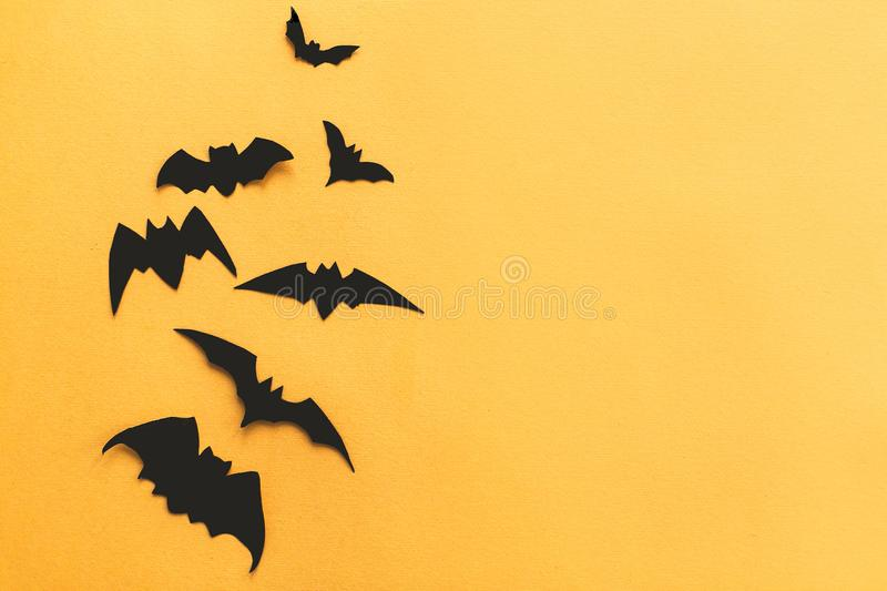 Halloween flat lay. Black bats  flying on bright yellow paper background, copy space. Modern spooky halloween decorations. stock photo