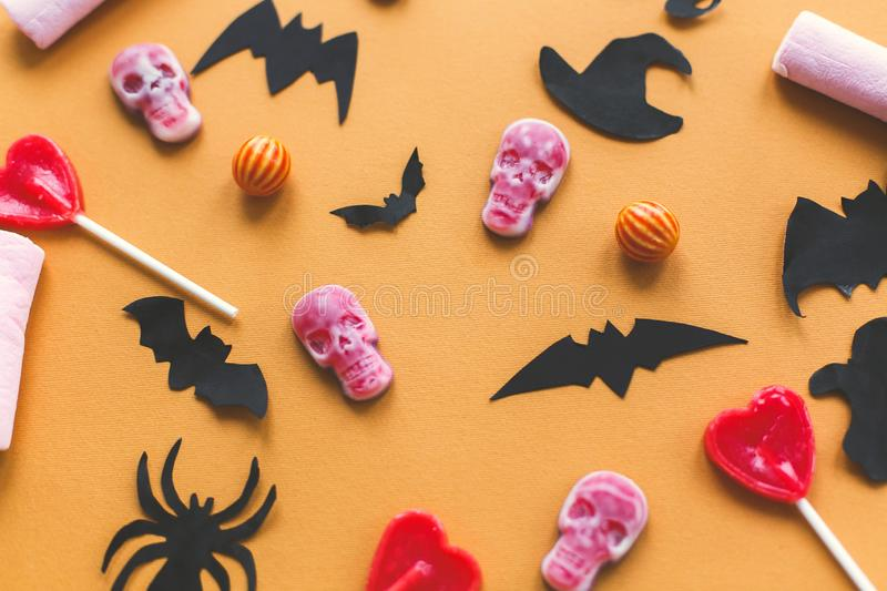 Halloween flat lay. Halloween candy skulls with black bats and ghost paper decorations on yellow background. Trick or treat stock image