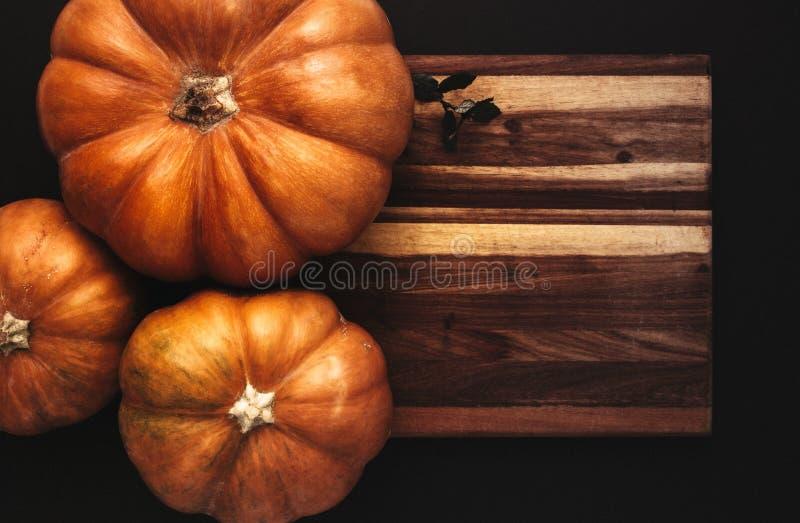 Halloween flat lay of pumpkins on wooden board stock illustration
