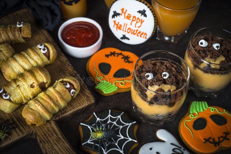 Halloween food assortment - sasage mummies, pumpkin dessert, gin royalty free stock photography