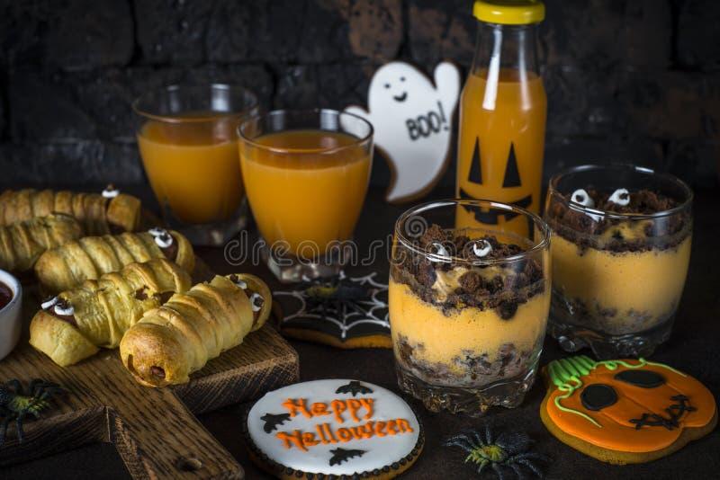 Halloween food assortment - sasage mummies, pumpkin dessert, gin stock images