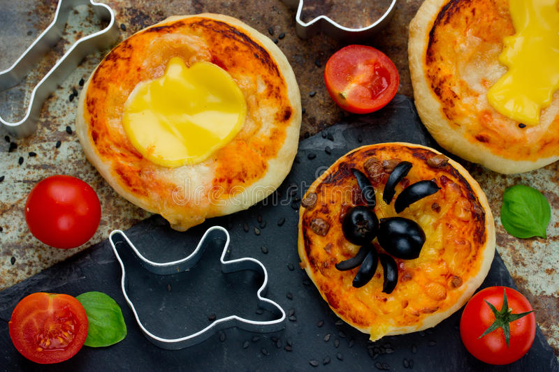 Halloween food ideas for kids party - pizza with tomato cheese o. Live top view royalty free stock image