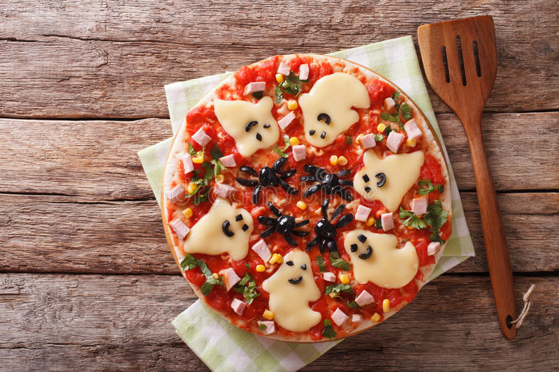 Halloween Food: Pizza with ghosts and spiders close-up. horizont royalty free stock photos