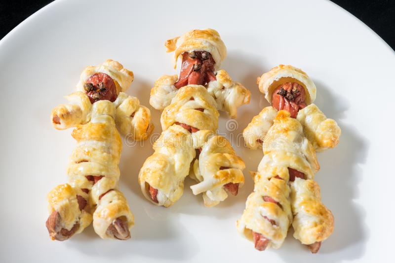 Halloween food. Sausage mummies in dough cooked in the oven. Halloween party appetizer and decoration stock images