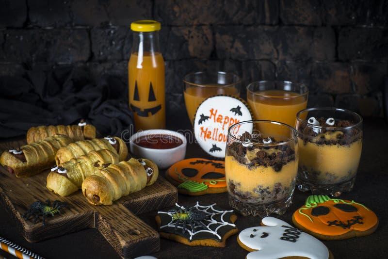 Halloween food assortment - sasage mummies, pumpkin dessert, gin royalty free stock photo