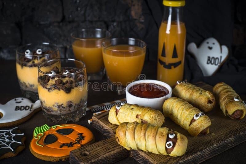Halloween food assortment - sasage mummies, pumpkin dessert, gin stock photos