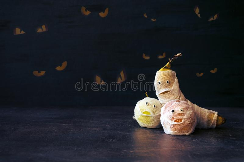 Halloween Fruit Mummy. Funny Scared orange, apple and banana with eyes and wrapped in bandages on dark background. Halloween DIY c stock photography