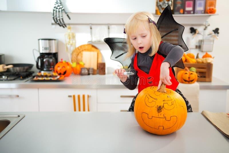 Halloween gekleed meisje die pompoen hefboom-o-Lantaarn creëren royalty-vrije stock afbeeldingen