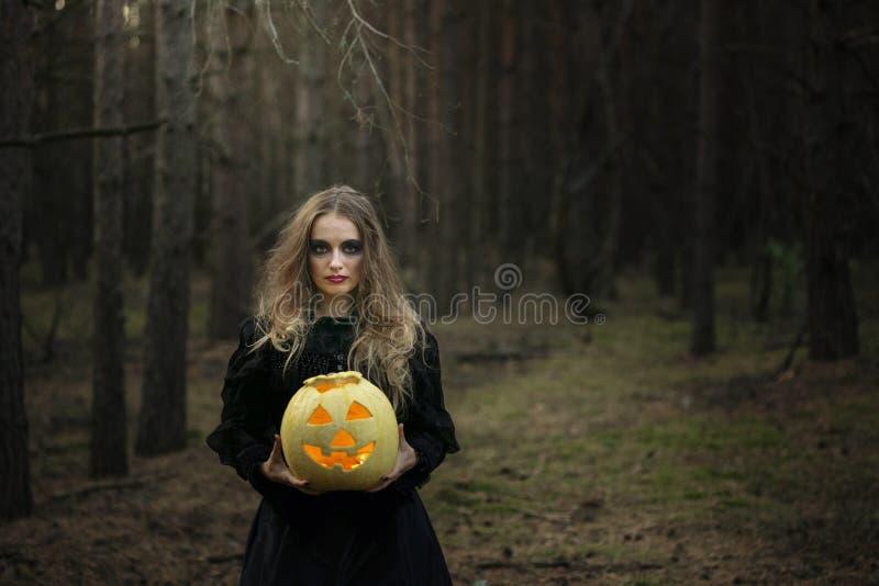 Halloween Gelber Kürbis Schönes Mädchen in einem schwarzen Kleid im Wald stockbilder